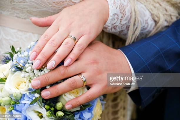 hands of the bride and groom on the wedding bouquet. gold wedding rings on the ring fingers of the newlyweds. - marryornot stock pictures, royalty-free photos & images