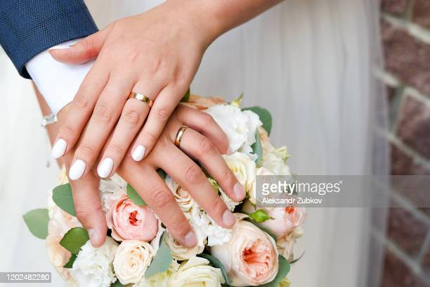 hands of the bride and groom on the wedding bouquet. - coniugi foto e immagini stock