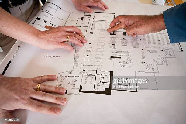 Hands of three people looking at blueprints