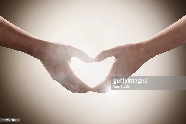 Hands of two people mading ??the shape of heart