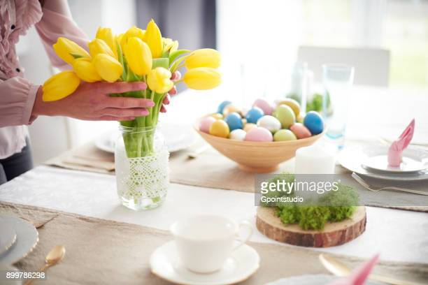 Hands of woman arranging yellow tulips at easter dining table
