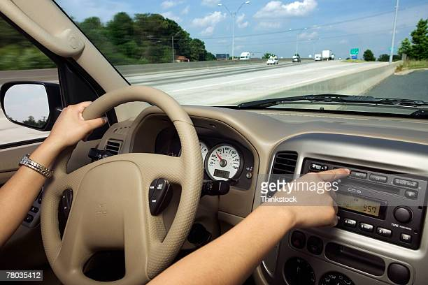 Hands of woman driving and using radio
