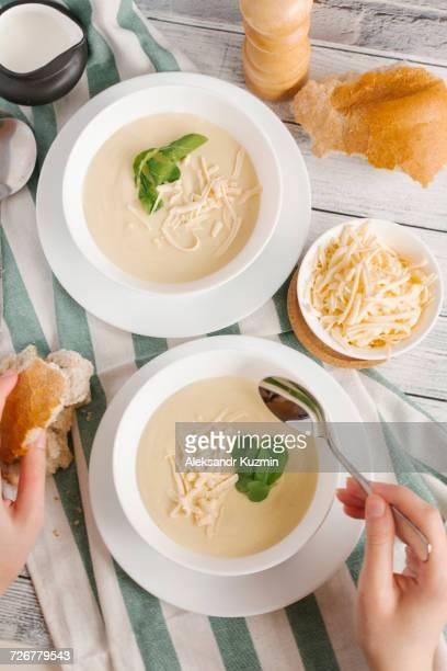 hands of woman eating bowl of cheese soup - sopa - fotografias e filmes do acervo