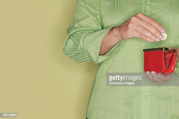 hands of woman holding change and change purse - red purse stock pictures, royalty-free photos & images