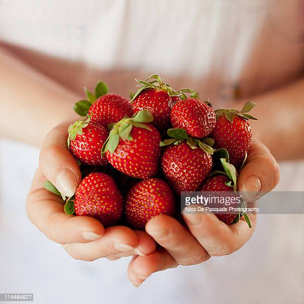 Hands of woman holding some strawberries