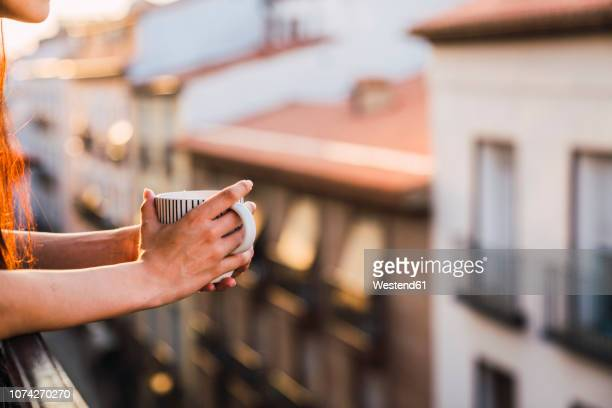 hands of woman on balcony above the city at sunset holding cup of coffee - europa meridionale foto e immagini stock