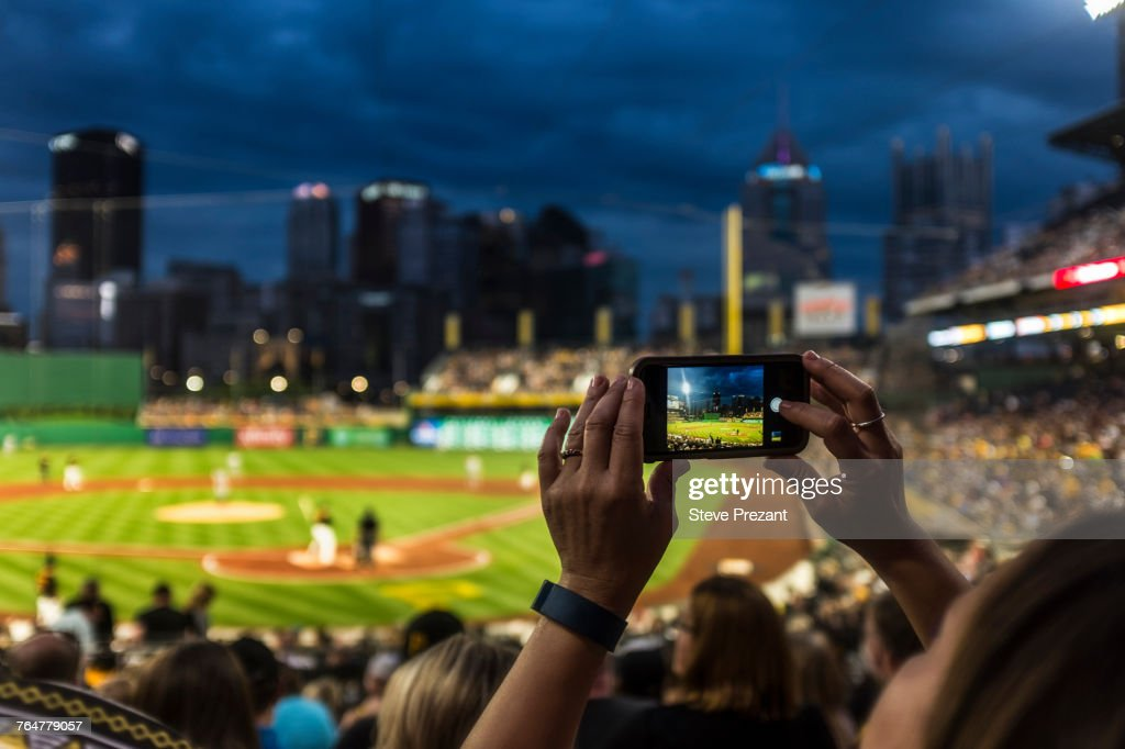 Hands of woman photographing baseball game with cell phone : Stock Photo