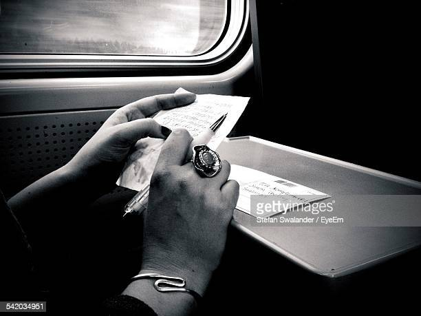 Hands Of Woman Reading Postcard In Train