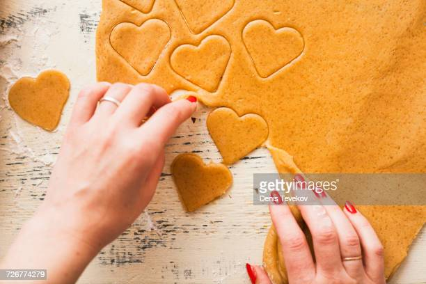 Hands of woman separating heart shapes cut from cookie dough