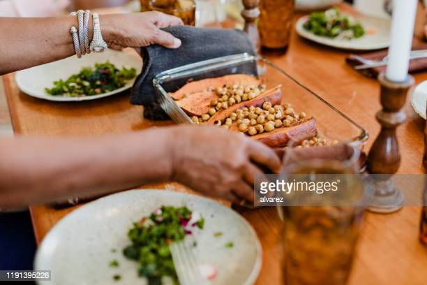 hands of woman serving vegan food on dining table - vegetarian food stock pictures, royalty-free photos & images