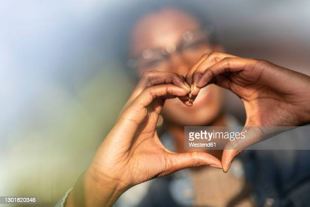 hands of woman showing heart sign - hand stock pictures, royalty-free photos & images