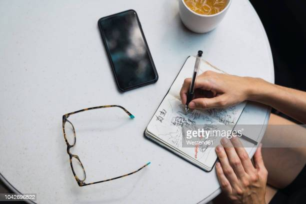 hands of woman sketching in notebook, glasses, tea and smartphone on table - skizze stock-fotos und bilder