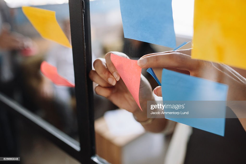 Hands of woman sticking adhesive notes on glass : Stock Photo