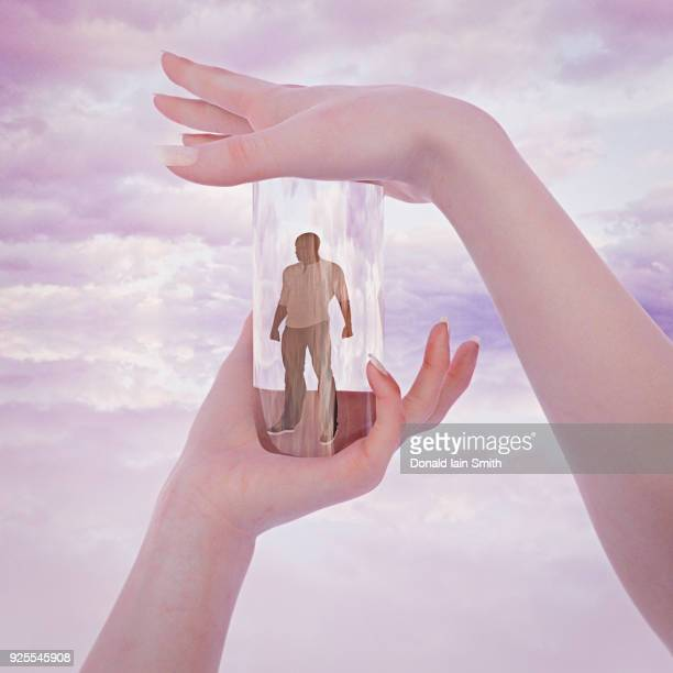 hands of woman trapping man in glass container - puppet stock photos and pictures