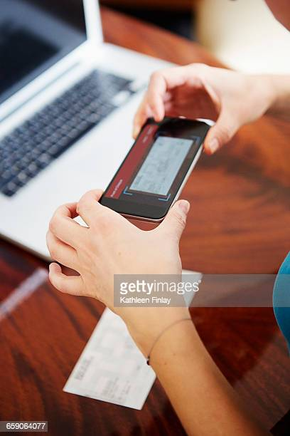 Hands of woman using smartphone to photograph cheque