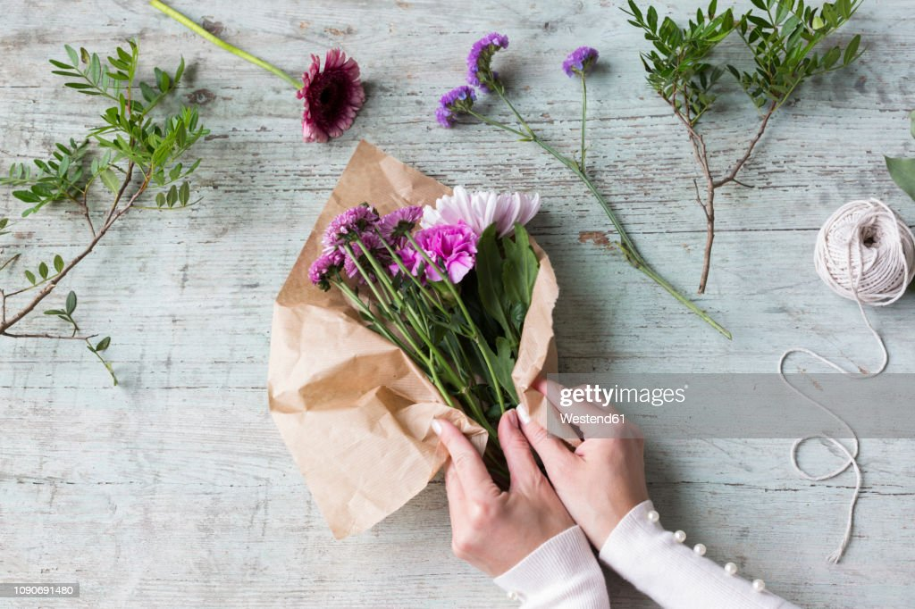 Hands of woman wrapping bunch of flowers : Stock Photo