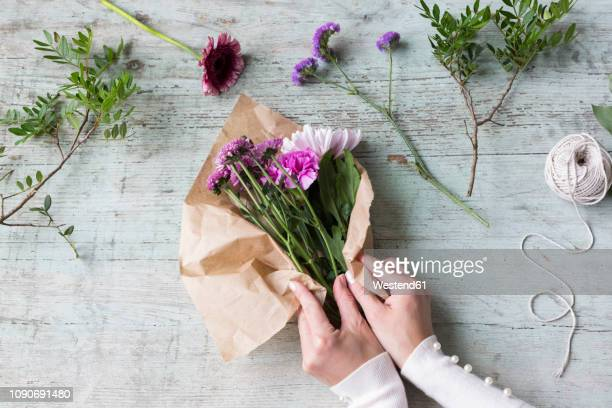 hands of woman wrapping bunch of flowers - bunch stock pictures, royalty-free photos & images