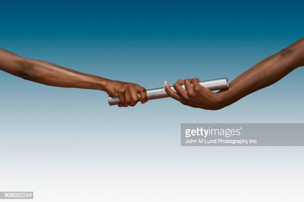 Hands of women passing baton on blue background