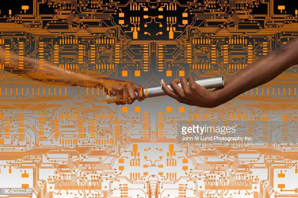 hands of women passing baton on circuit board - relay baton stock photos and pictures