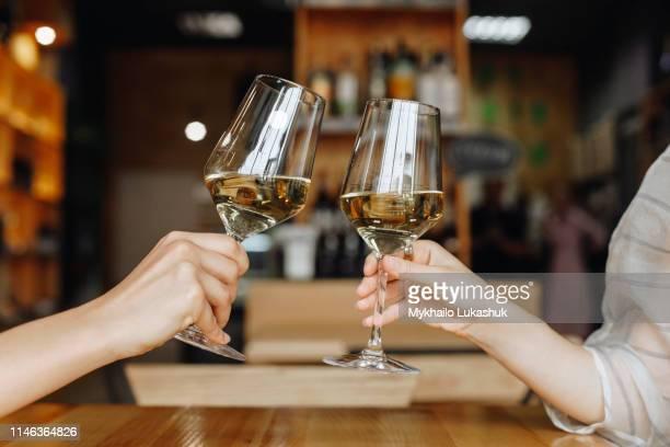 hands of women toasting with glasses of white wine - ワイナリー ストックフォトと画像