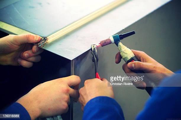 Hands of workers being welded