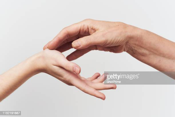 hands of young and old women on a light background - touching stock pictures, royalty-free photos & images