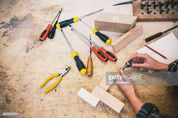 Hands of young craftswoman holding component in pipe organ workshop
