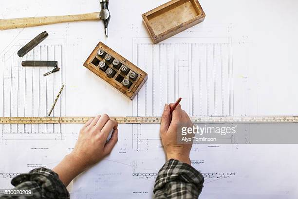 Hands of young craftswoman measuring blueprint in pipe organ workshop