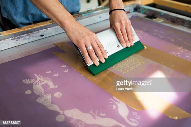 Hands of young male printer using squeegee in printing press studio