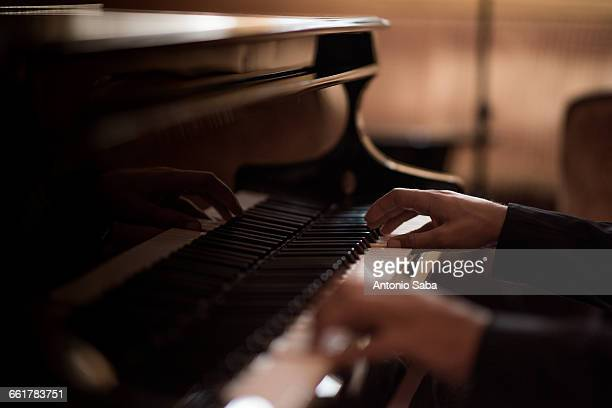 hands of young man playing piano keys in bar at night - ピアノ ストックフォトと画像
