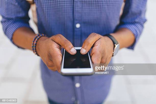 Hands of young man using smartphone