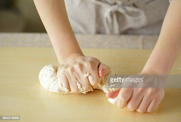 Hands of young woman kneading bread dough,close up