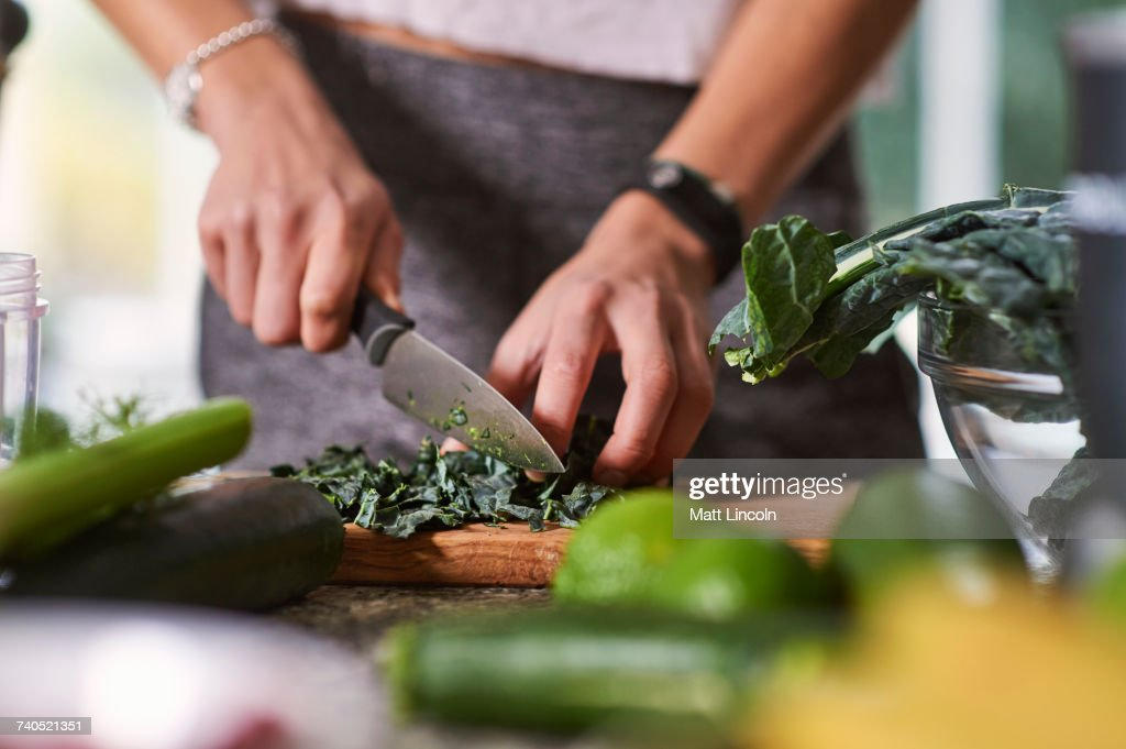 Hands of young woman slicing cabbage at kitchen table : Stock Photo
