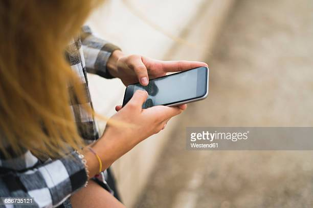 Hands of young woman text messaging