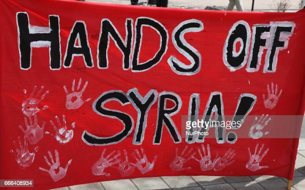 'Hands Off Syria' sign during a protest against US President Donald Trump's decision to launch airstrikes against Syria on April 8 2017 in Toronto...