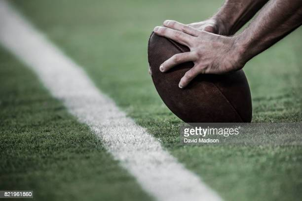 hands on an american football - football stockfoto's en -beelden
