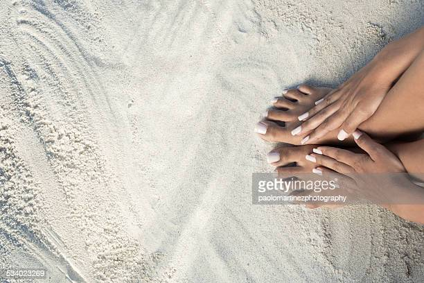 Hands on bare feet on a white beach