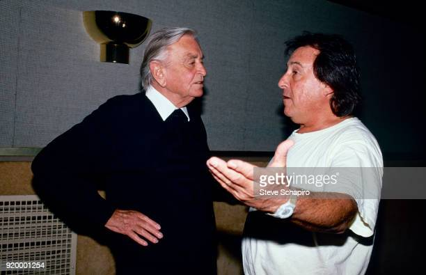 Hands on his hips, British film director David Lean listens to American film director Paul Mazursky as they speak in a hallway, Los Angeles,...