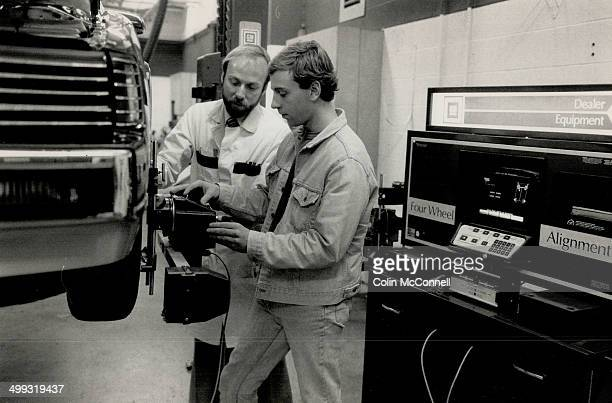 Hands on Instructor Peter Lokum explains a wheel alignment technique to Al Carr a student in the new Automotive Service Educational Program at...
