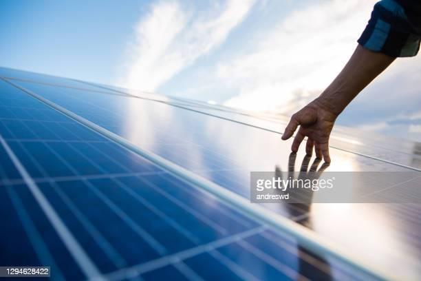 mani sul pannello solare che genera energia - pannelli solari foto e immagini stock
