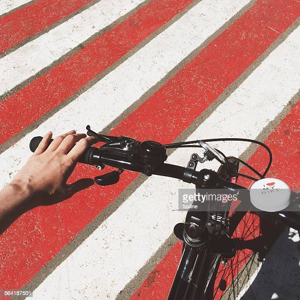 Hands on the handlebars of a bike on a striped road