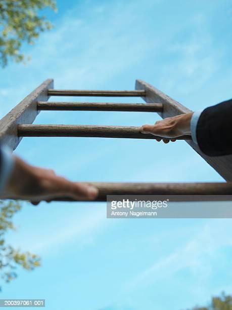 Hands on wooden ladder