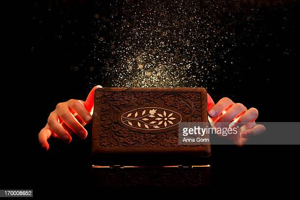 Hands open wooden box as sparkles fly out