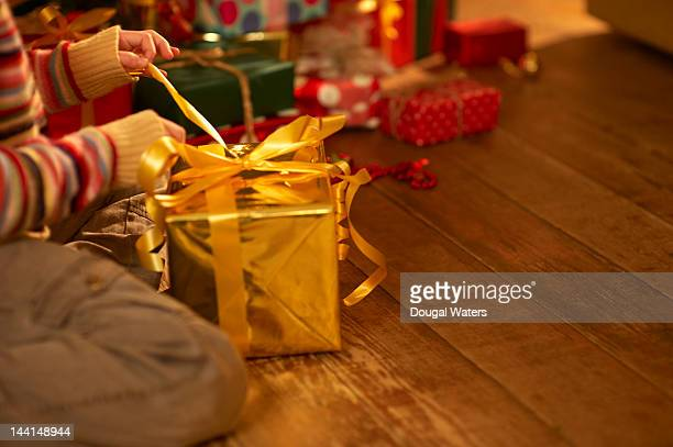Hands opening christmas present.
