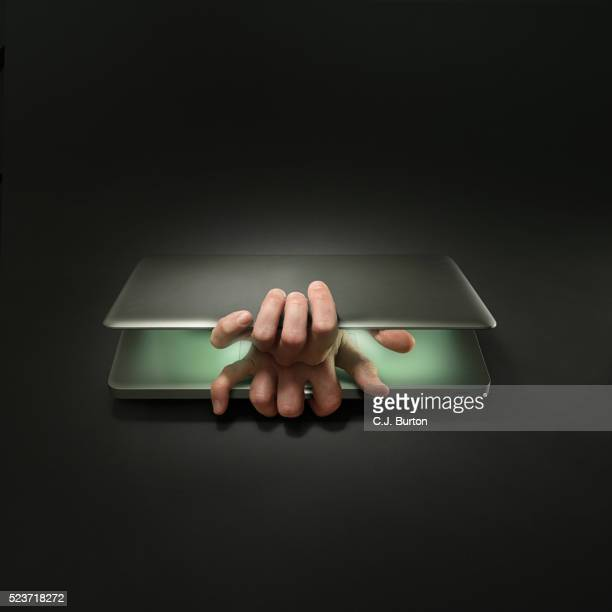 Hands opening laptop from inside