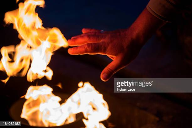hands over eternal flame at field of mars - eternal flame stock photos and pictures