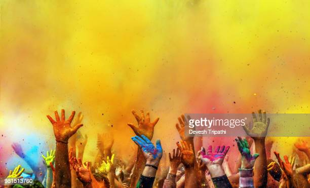 hands painted with different colors raised up on holi festival, washington dc, usa - feiern stock-fotos und bilder
