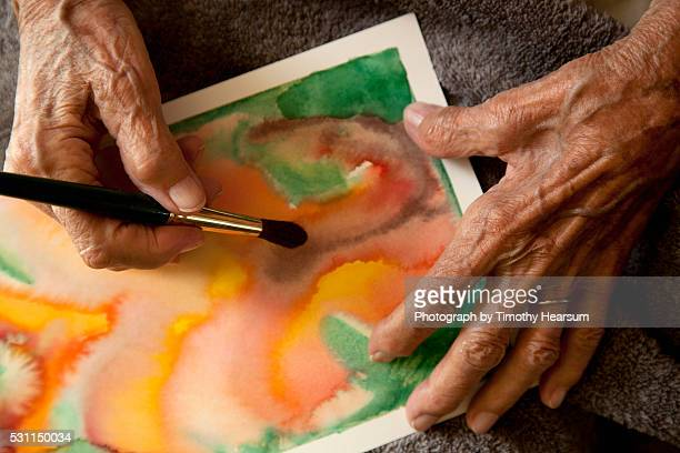 hands painting watercolor - timothy hearsum stock pictures, royalty-free photos & images