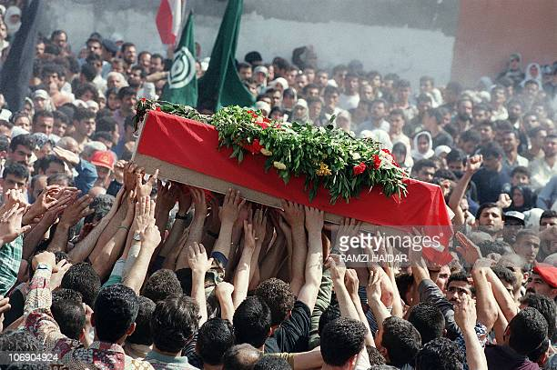 Hands pass along a coffin 30 April 1996 in Qana southern Lebanon during the burial ceremony for 105 civilians killed in an Israeli artillery attack...