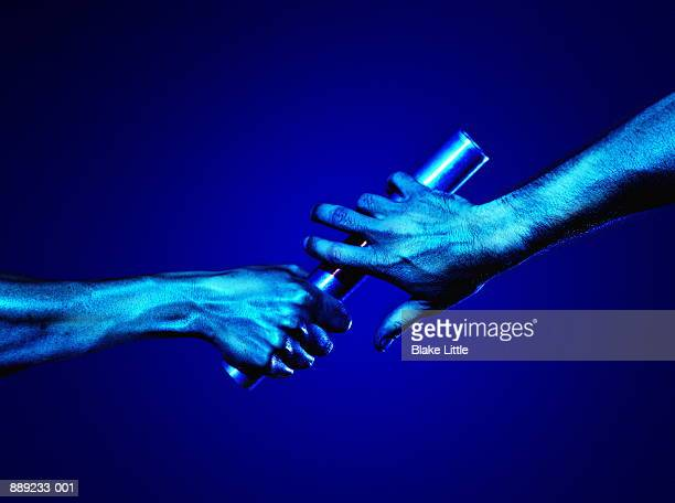 hands passing baton (blue tone) - passing sport stock pictures, royalty-free photos & images